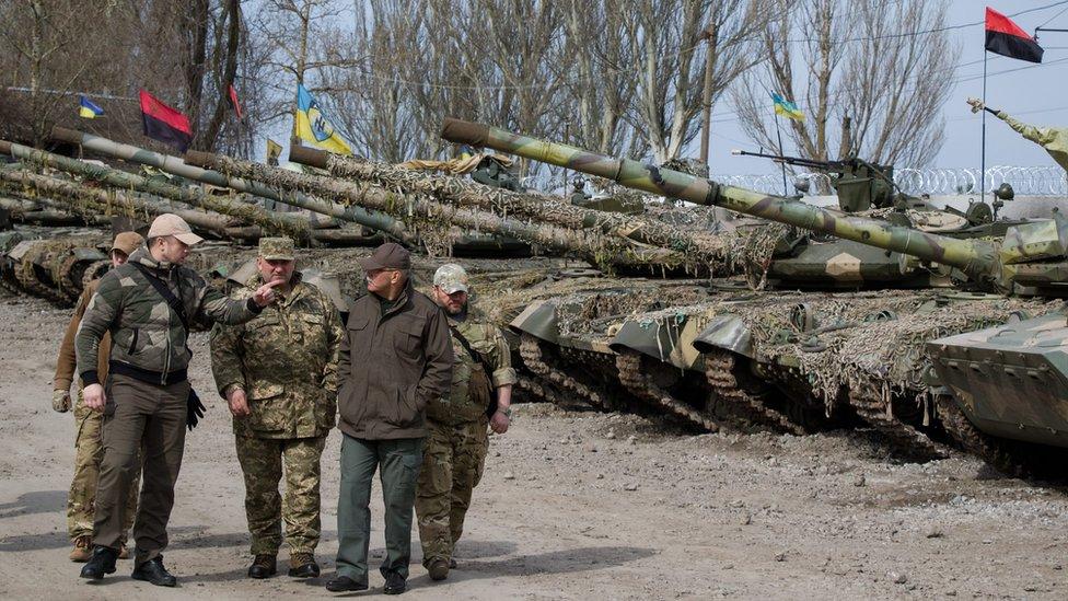 Ukrainian officers walk past a tank line from the volunteer Azov battalion (6 April)