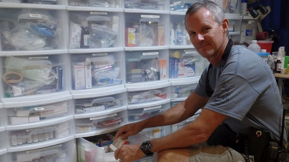 Jonathan Cornelius in front of the medicine cabinets in the clinic