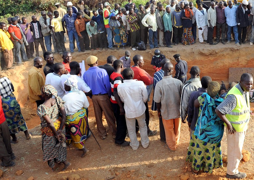 People in Dogo Nahaw, a village south of Jos, gather at the scene of a mass burial of their kinsmen killed during a religious crisis in March 2010