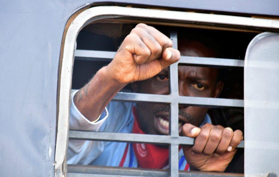 Robert Kyagulanyi, also known as Bobi Wine, raises his fist through the bars of a police van.