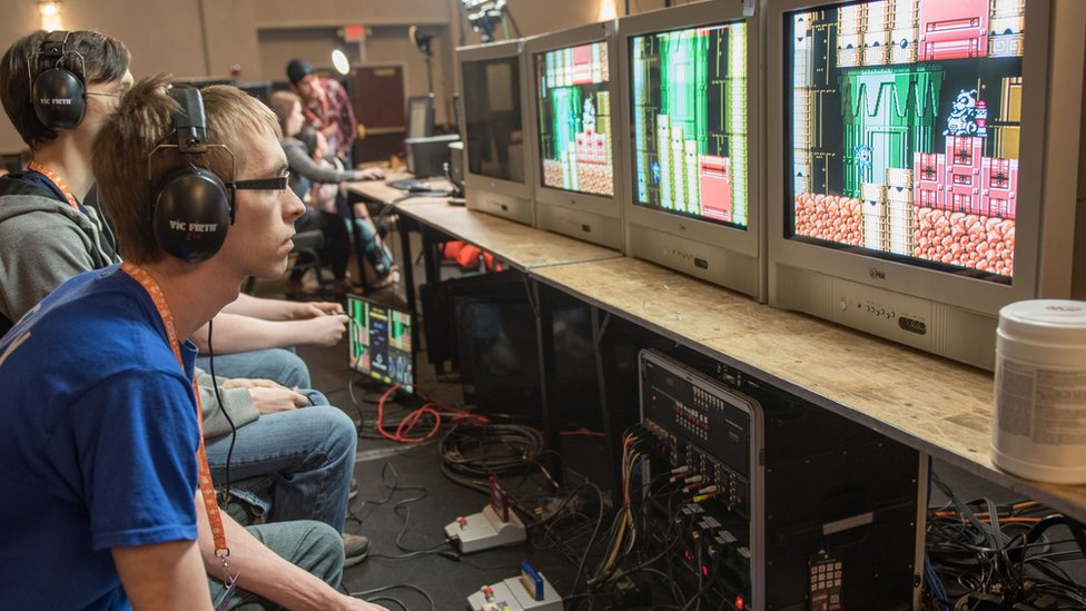 Three people are playing games sat side-by-side. They are staring at their own separate monitors. On the floor are several SNES consoles connected to the TVs.