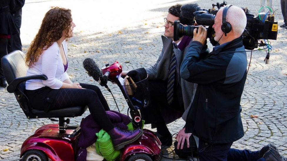 Kaliya Franklyn in her electric scooter talking to a TV crew