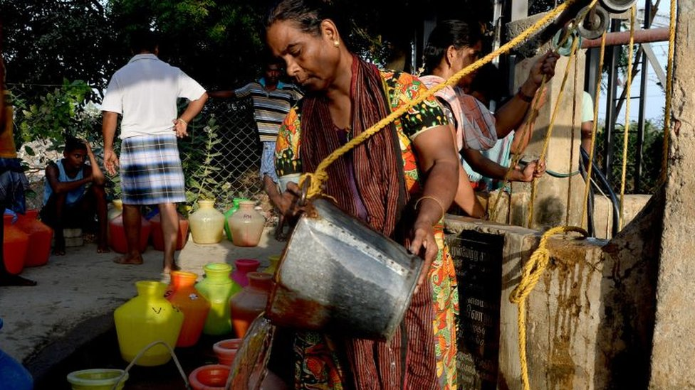 Woman pours water into pots