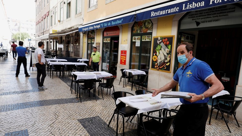 A waiter waits for customers at a restaurant, amid the coronavirus disease (COVID-19) outbreak, in downtown Lisbon, Portugal May 25