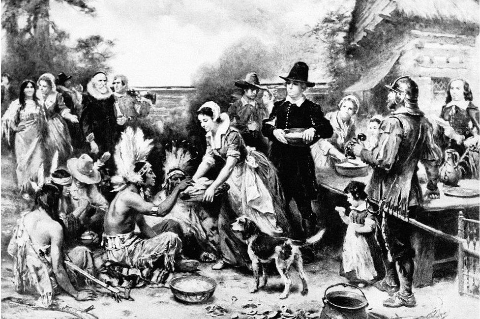 An artists depiction of the first Thanksgiving meal, featuring Native Americans