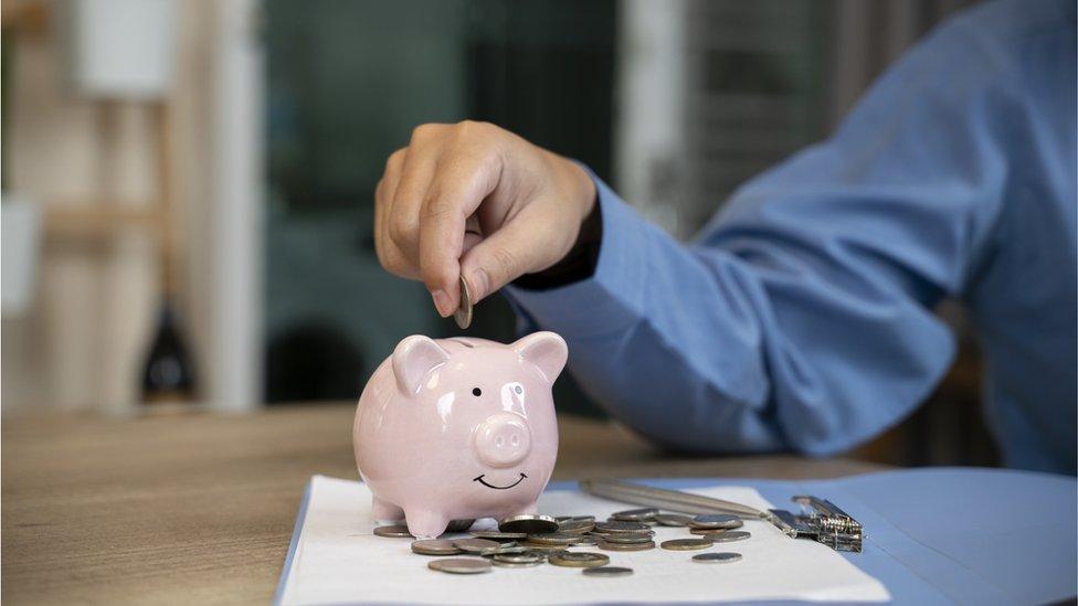 Una persona pone dinero en una alcancía.