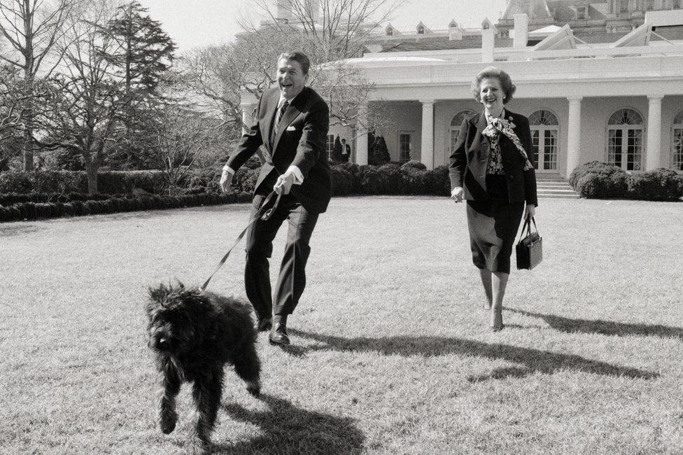 الرئيس رونالد ريغان ورئيسة الوزراء البريطانية مارغريت تاتشر يمشيان كلب ريغان لاكي في حديقة البيت الأبيض عام 1985.