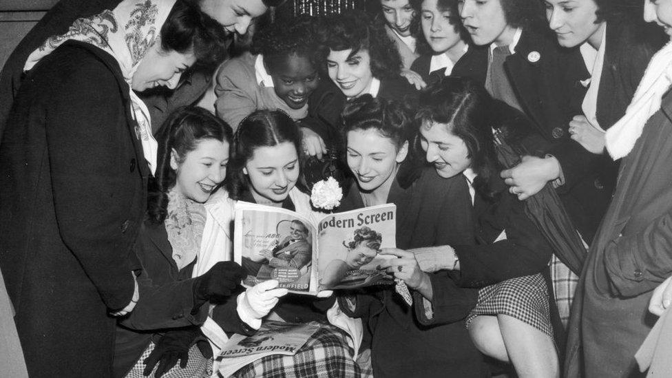 Un grupo de mujeres jóvenes lee una revista Modern Screen sobre farándula en 1950 en Nueva York.