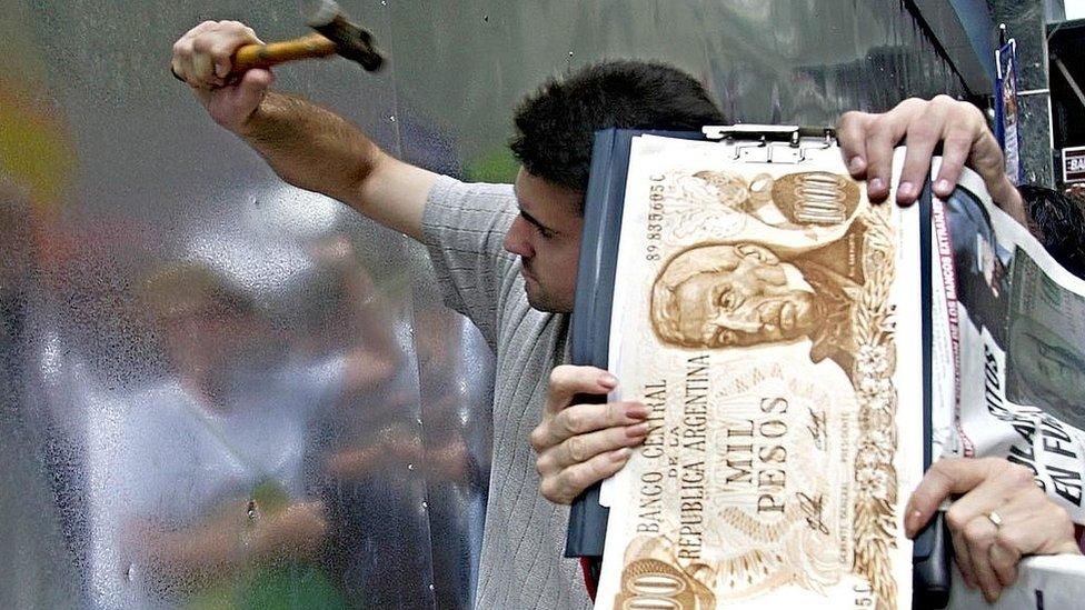 Joven en Argentina amartillando la puerta a un banco durante la crisis de el corralito.