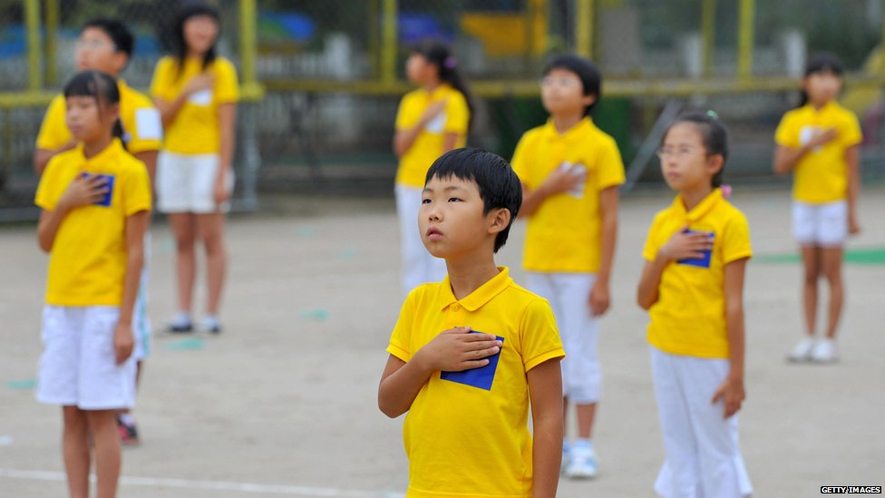 South Korean schoolchildren stand to attention during their national anthem