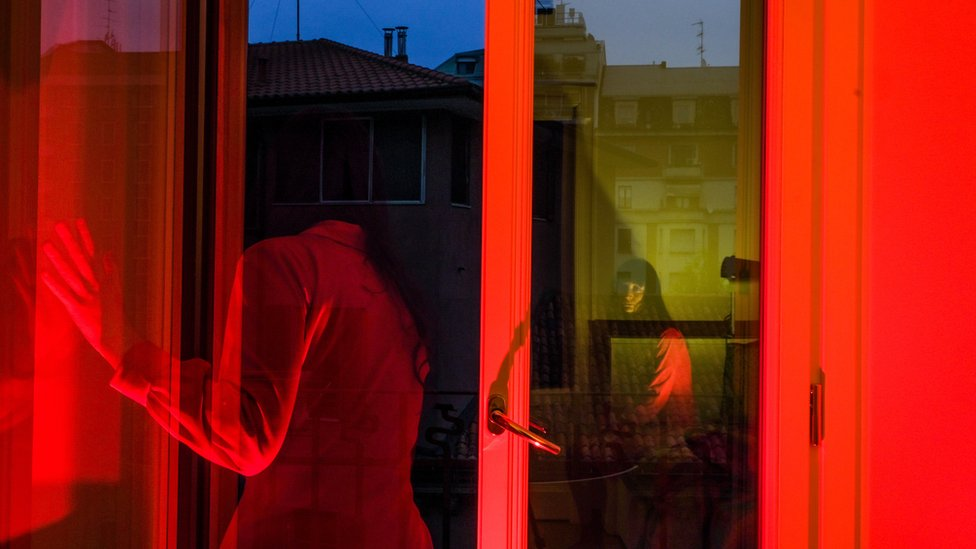 A red-tinted photograph shows Lucia staring outside of her window