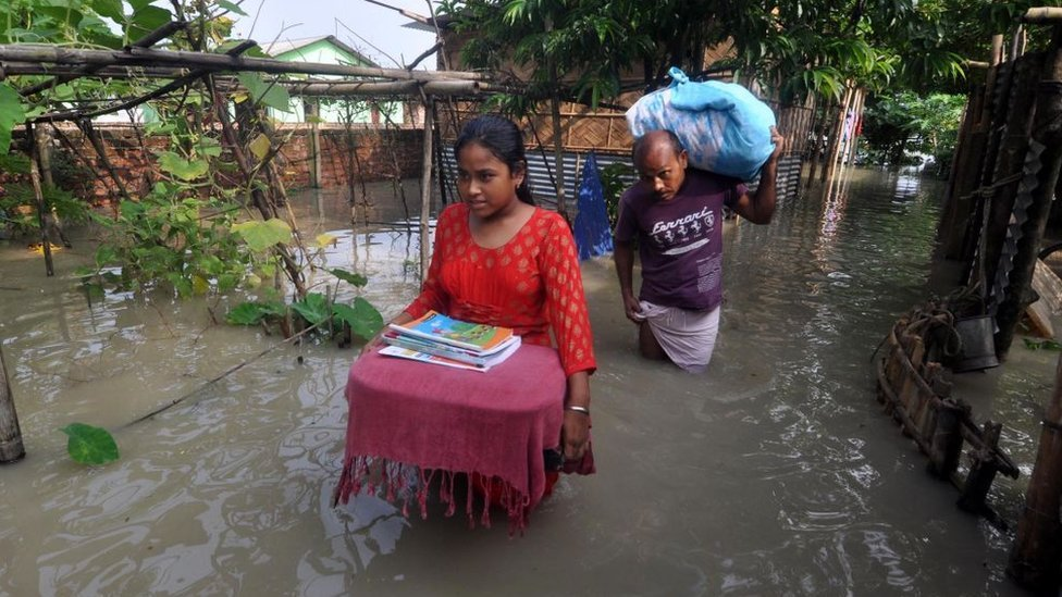 Villagers move to a safer place from the flooded area of Hatisela in Kamrup district of Assam.