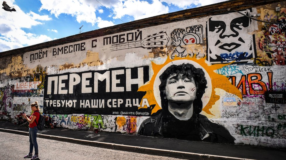 Tourists take photos in front of a Tsoi Wall, a memorial to Viktor Tsoi, in downtown Moscow