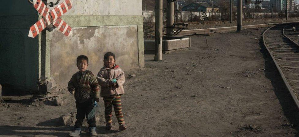 Niños frente a un ferrocarril en la ciudad de Chongjin, en el noreste de Corea del Norte, 21 de noviembre de 2017