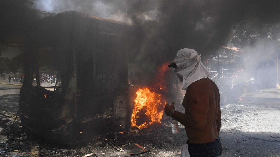 Pendukung oposisi Juan Guaido berdiri di samping sebuh bus yang terbakar di Caracas