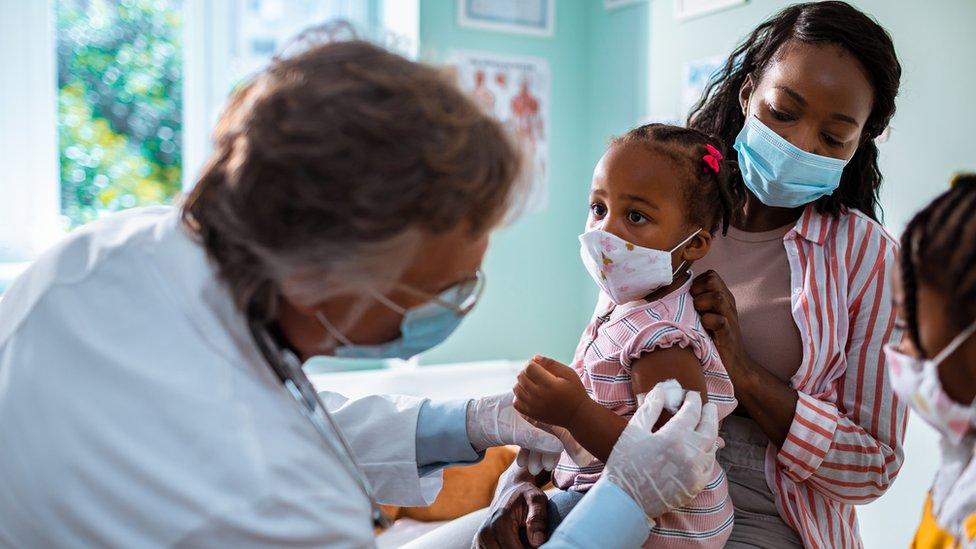 Una niña recibiendo una vacuna.