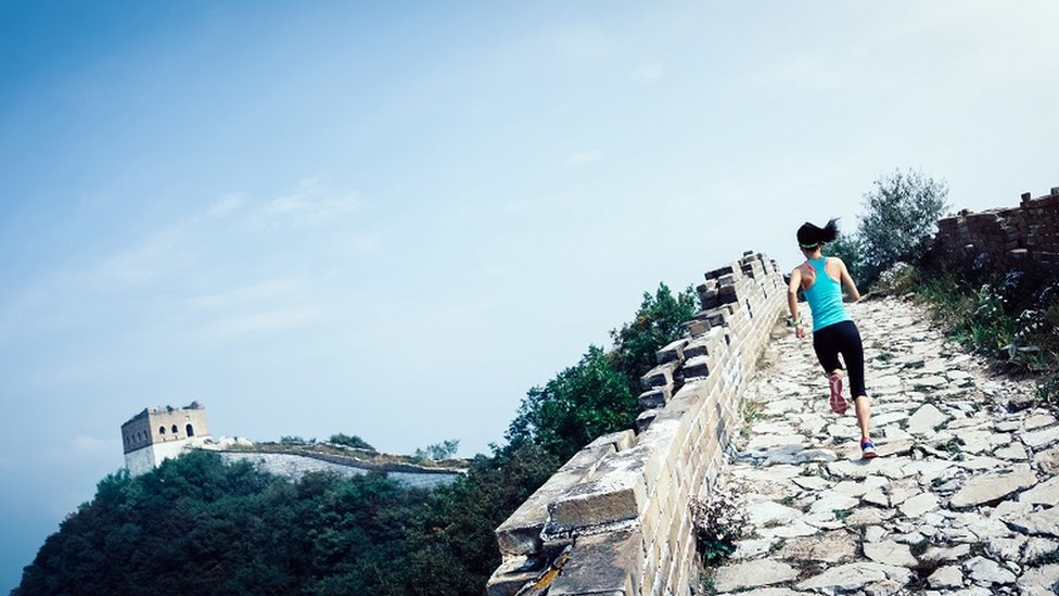 žena trči kineskim zidom