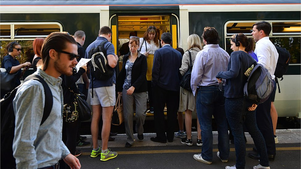 People disembark and wait to board a train on the hugely-reduced Southern rail service