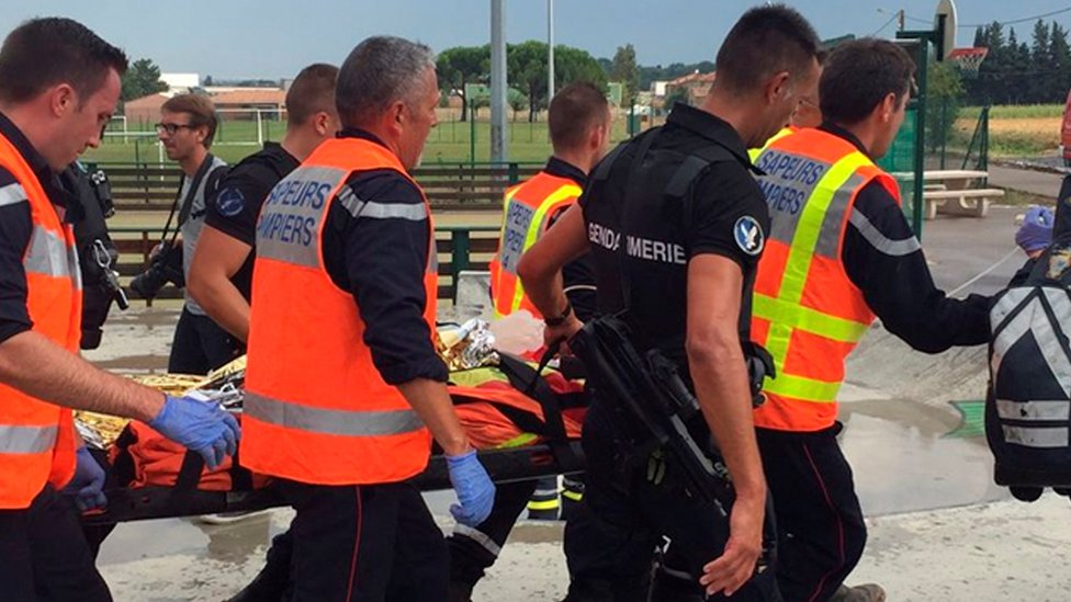 Firemen take a badly injured passenger to a helicopter to be airlifted to hospital (17 Aug)