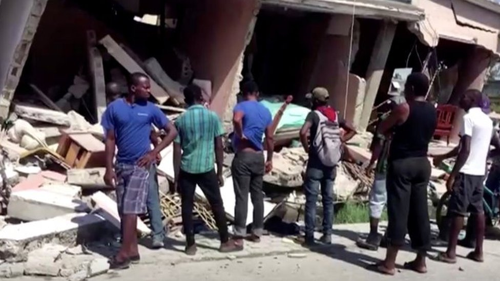 People stand in front of a collapsed building following an earthquake