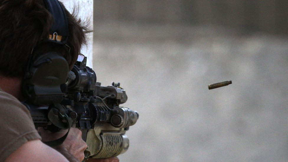 A US Special Forces soldier shoots with an assault rifle on a firing range