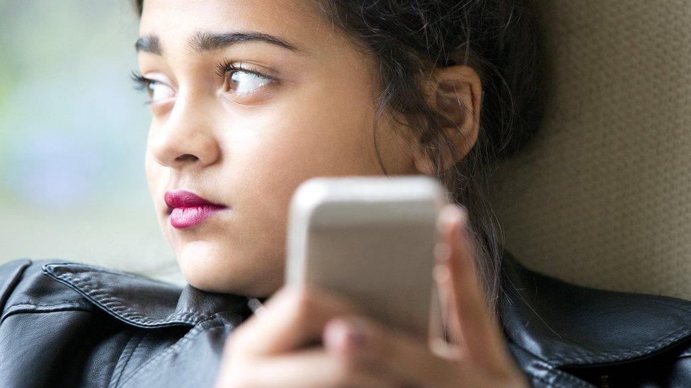 Una joven con su teléfono.