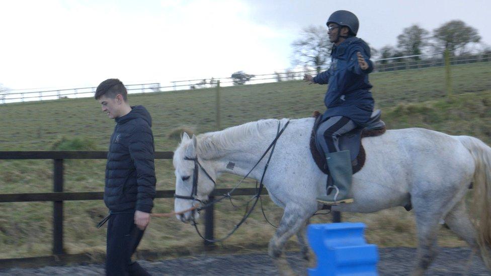 Dos jóvenes con un caballos