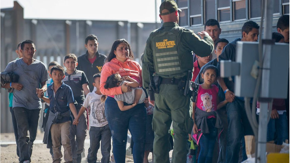 Migrants are loaded onto a bus by U.S. Border Patrol agents after being detained when they crossed into the United States from Mexico