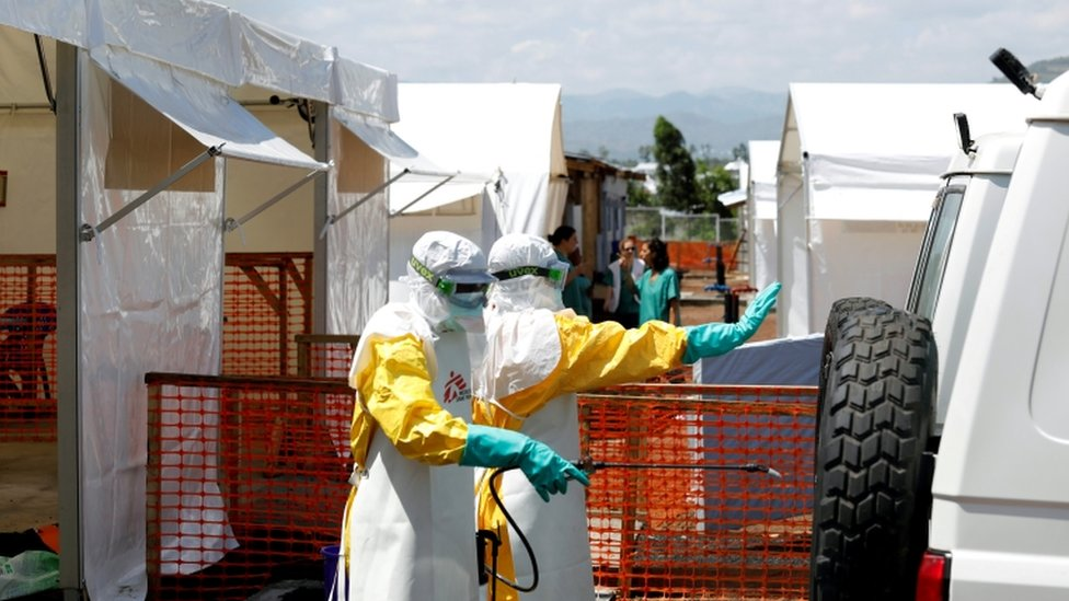 Health workers dressed in protective suits disinfect an ambulance at an Ebola treatment centre in DR Congo
