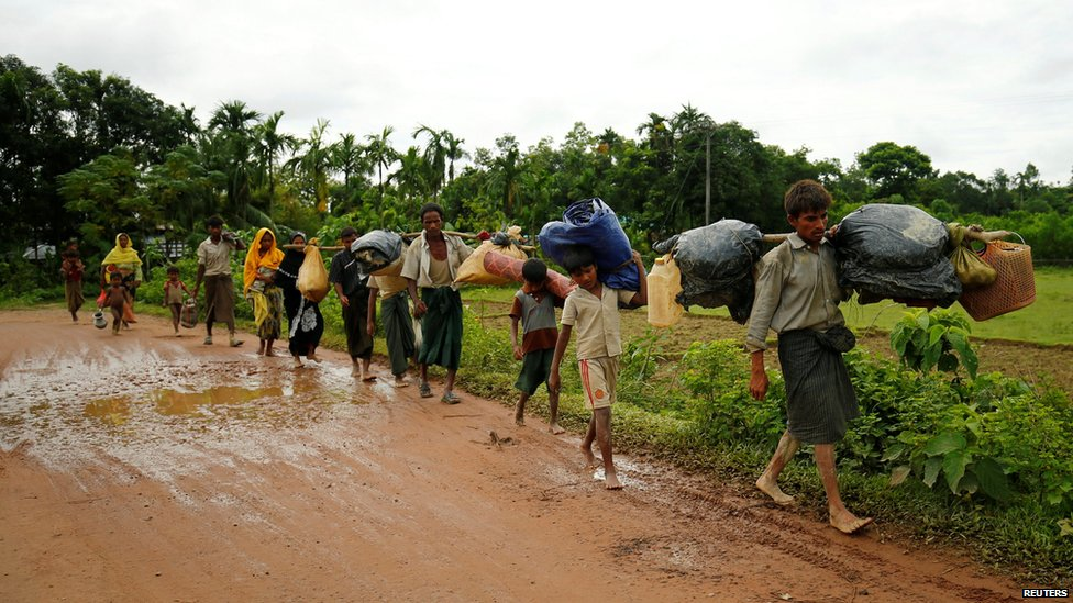 "Rohingyas walk along the road to reach to the refugee camp after crossing the border in Cox""s Bazar"