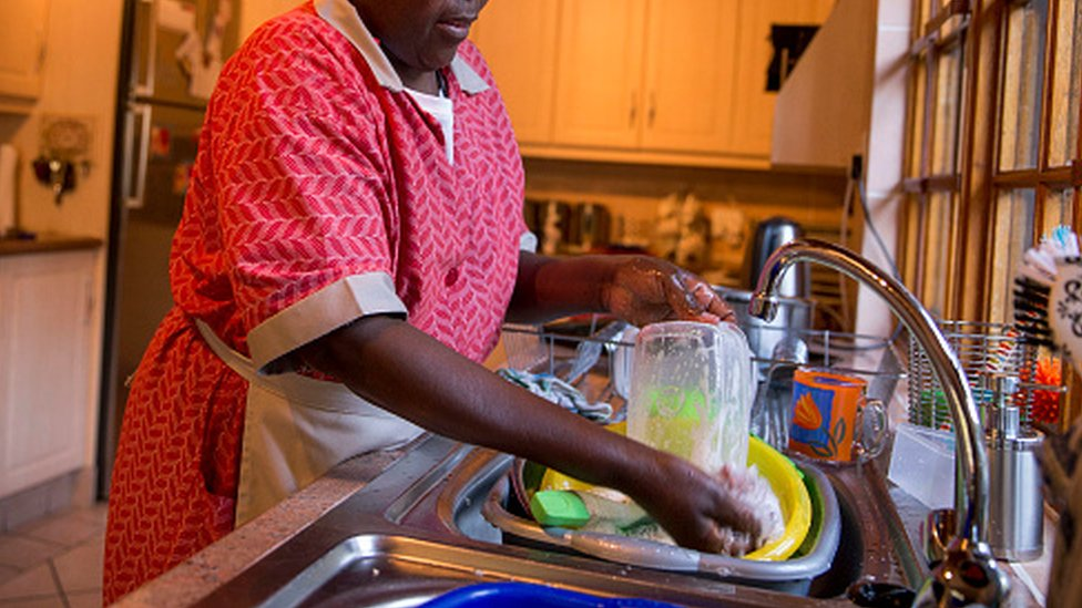 A domestic worker washes plates