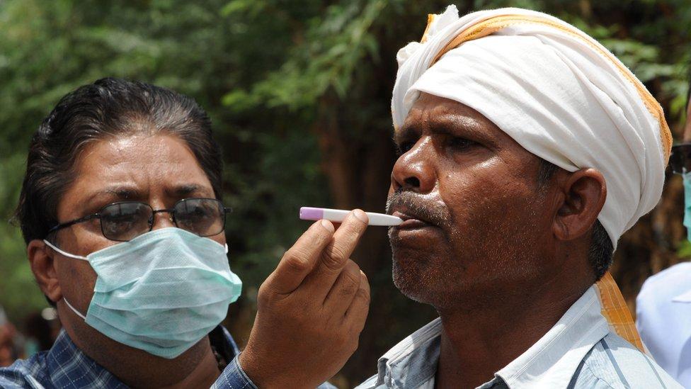 Un doctor examina a un paciente con fiebre en India.
