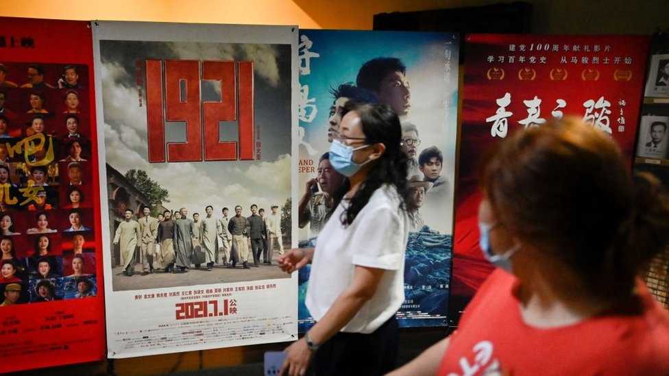 People walk past a poster for '1921', a film about the founding of the Communist Party of China in the same year, ahead of the Chinese Communist Party's 100th founding anniversary at a cinema in Beijing.