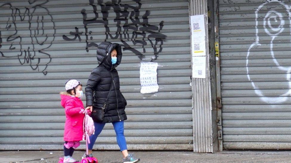 أشخاص يرتدون كمامات يمرون أمام متجر مغلق