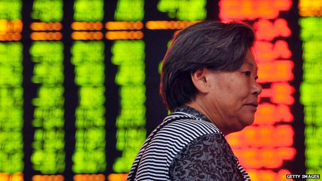 A Chinese investor walks in front of a screen showing share prices at a securities firm in Hangzhou, eastern China