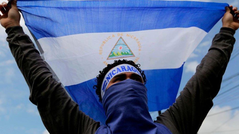 Un joven sostiene una bandera de Nicaragua.