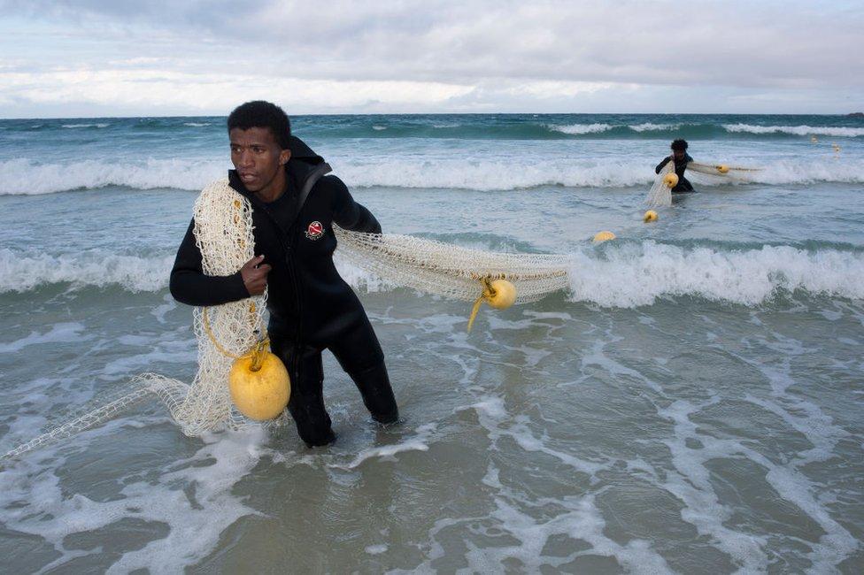 Two men haul in a large net.