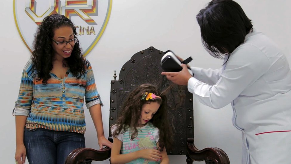 Nurse taking off VR headset from young girl while mother looks on