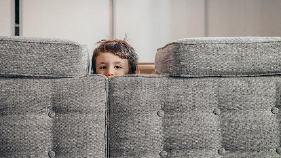 Un niño juega en el sofá