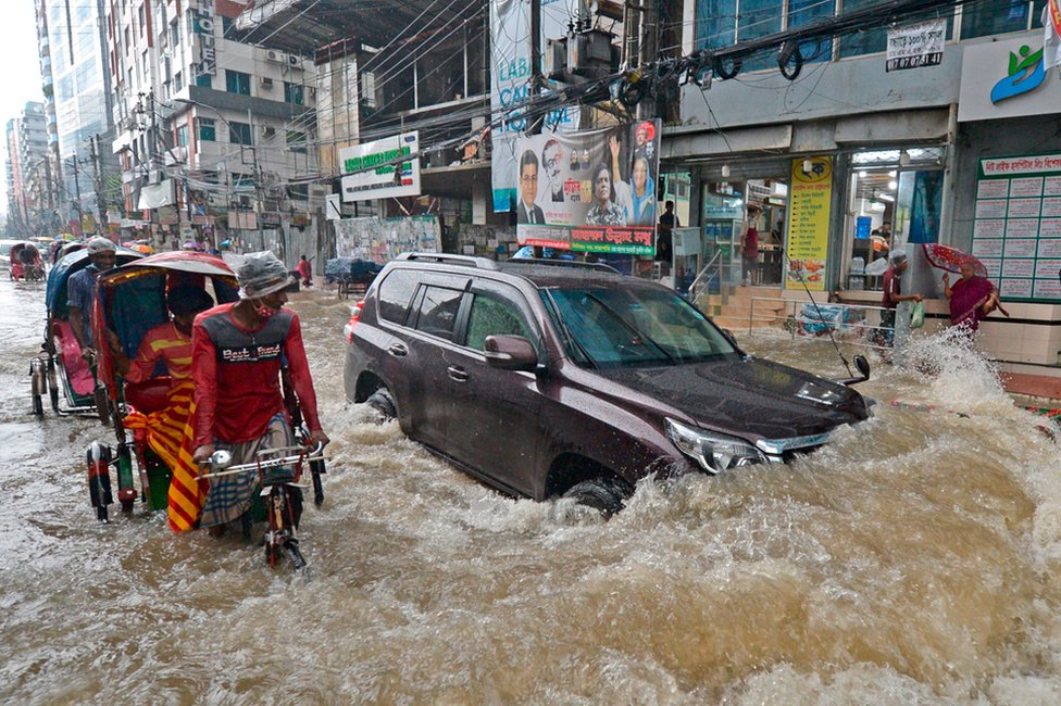 Commuters make their way through a water-logged street