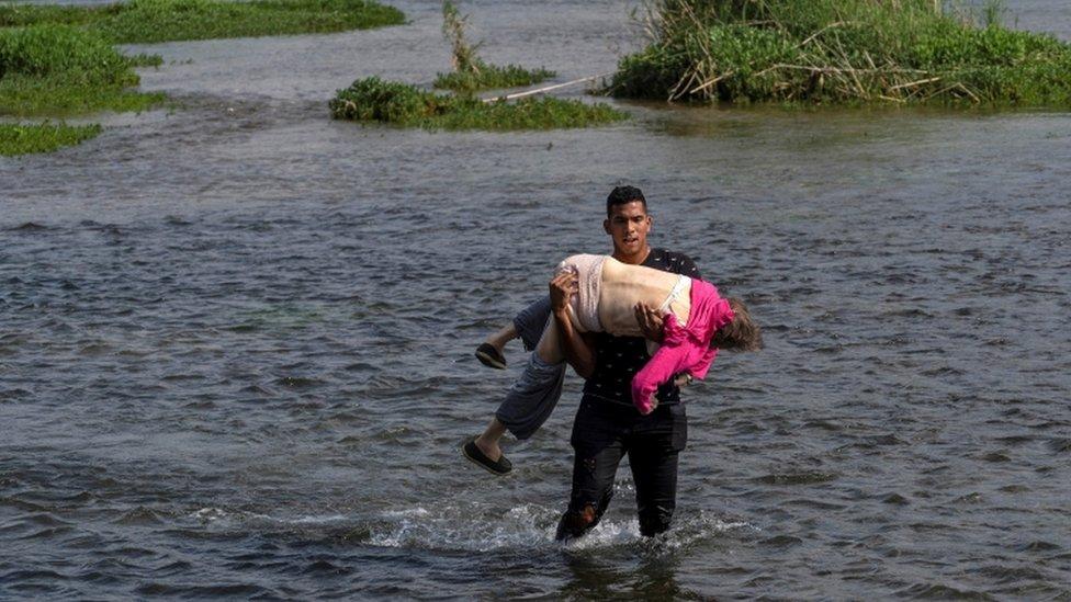 Venezolano cruzando el río Grande con una mujer en brazos.