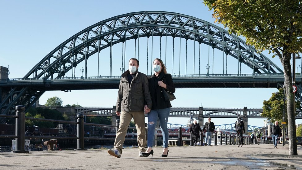 Couple wearing masks walking along Newcastle Quayside with Tyne Bridge in the background