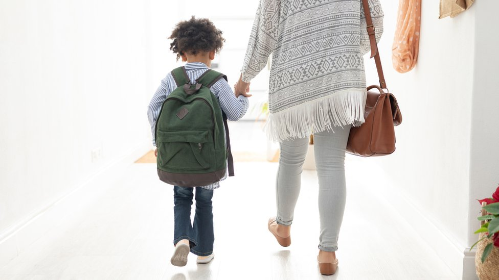 Niño camina de la mano con la mujer.