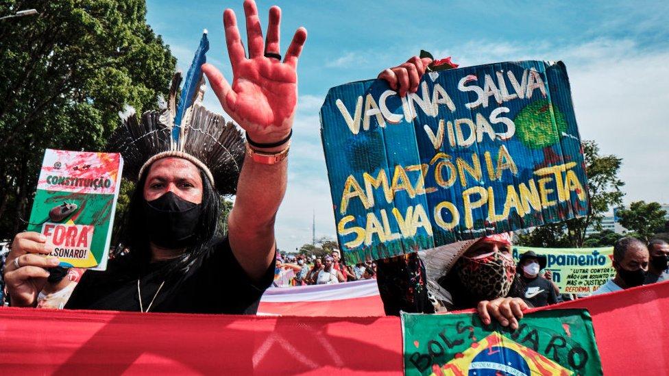 Manifestantes sostienen carteles durante una protesta contra el presidente Jair Bolsonaro en Brasilia el 29 de mayo de 2021