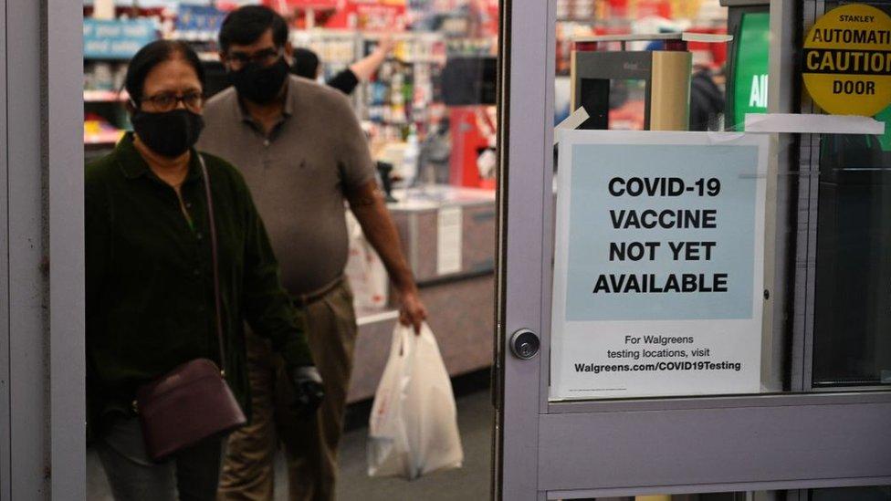 Placa em porta de farmácia diz que 'Vacina para covid-19 ainda não está disponível'