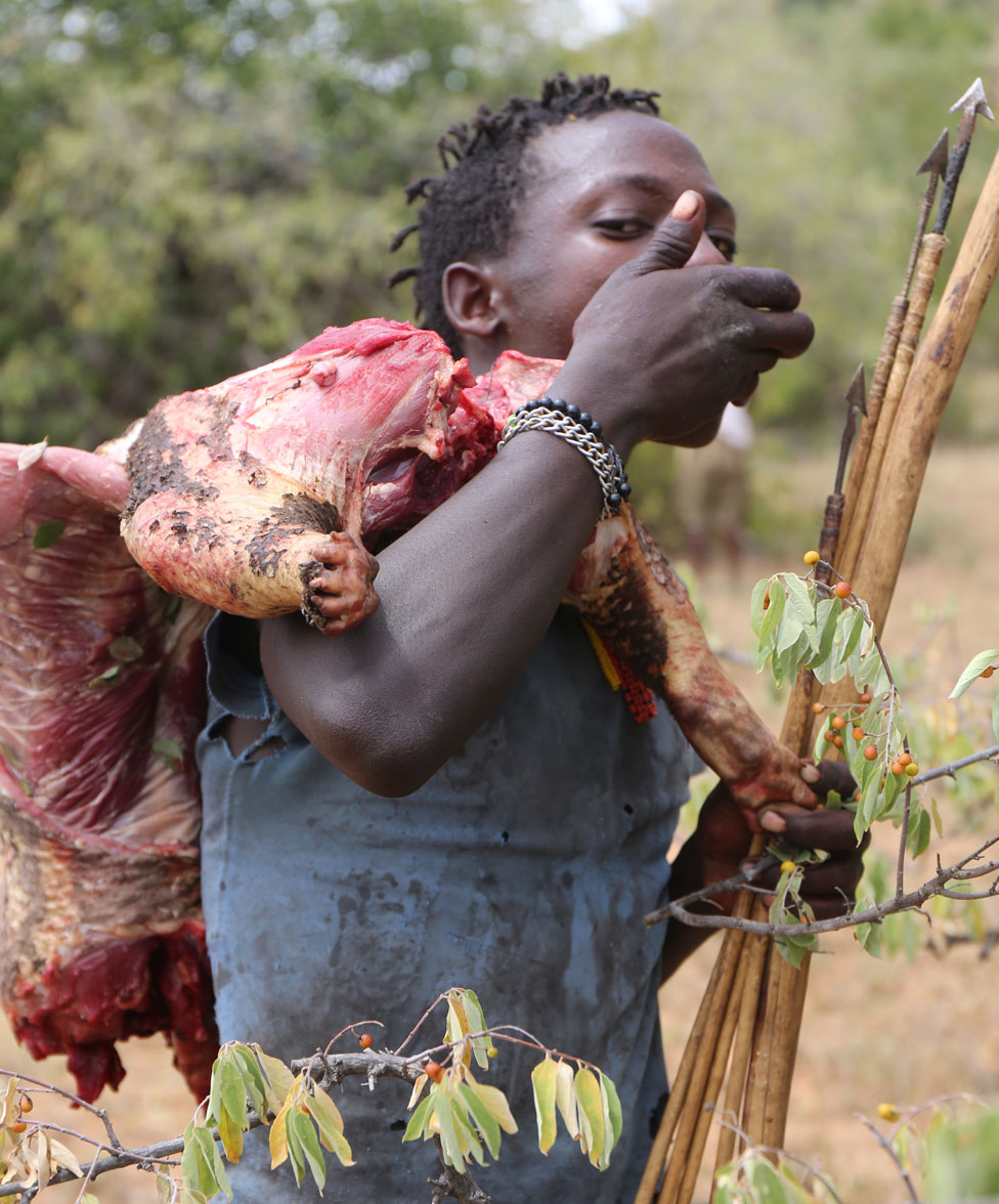 Hadza man carrying meat and arrows