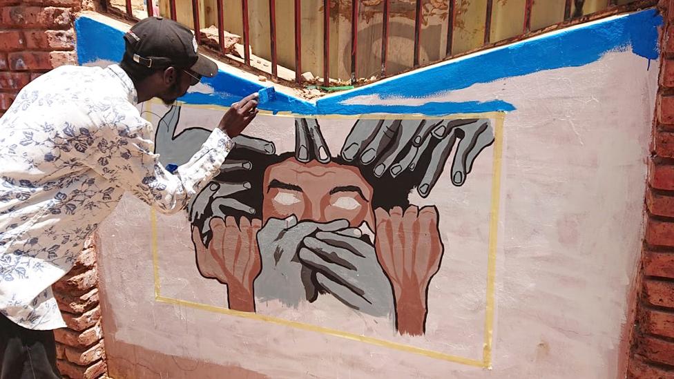 A student painting a mural in Khartoum, Sudan