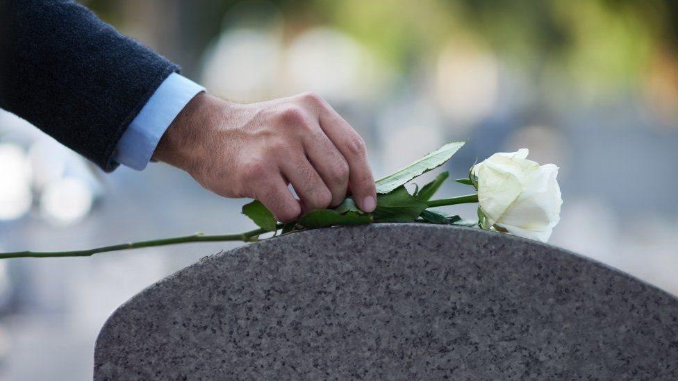 رجل يضع وردة على شاهد مقبرة