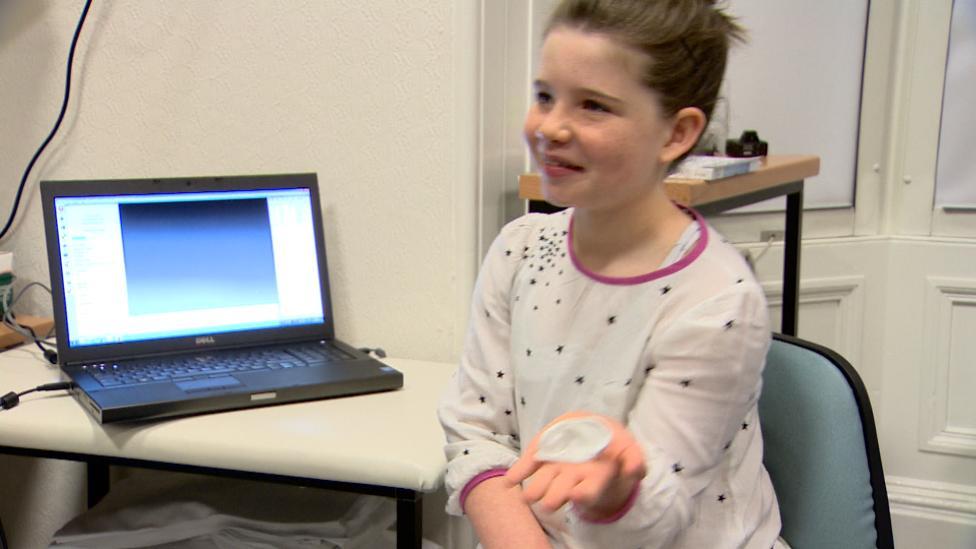 Anya Storie holds 3D model ear