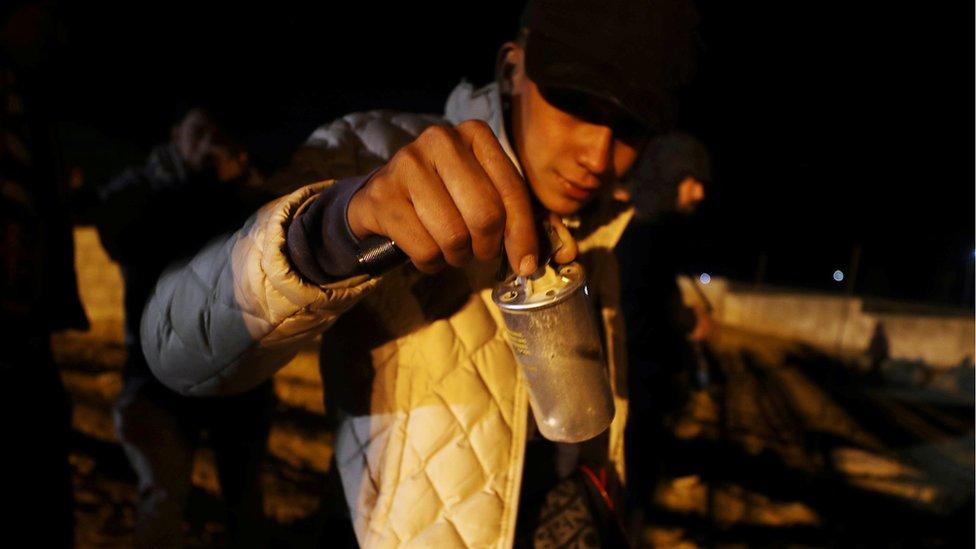 Migrante con una bomba lacrimógena en la frontera entre EE.UU. y México
